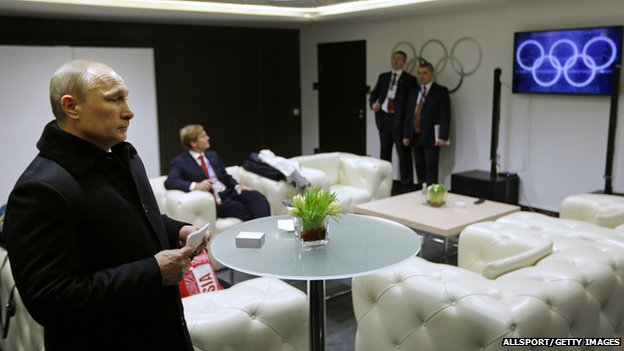 Russian President Vladimir Putin waits in the presidential lounge to be introduced at the opening ceremony of the Sochi 2014 Winter Olympics as a television screen displays five Olympic rings (7 February 2014)