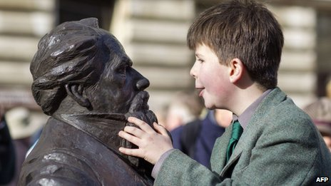 Oliver Dickens, nine, with a statue of his great, great, great grandfather Charles Dickens in Portsmouth