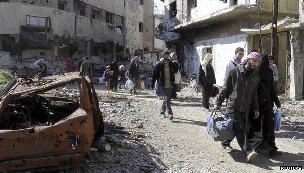 Civilians carry their belongings as they walk towards a meeting point to be evacuated from a besieged area of Homs (7 February 2014)