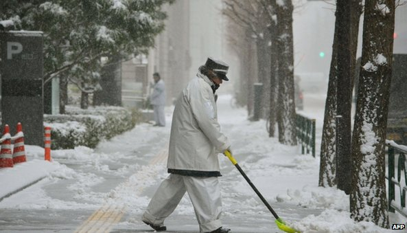 A worker removes snow from a pavement in Tokyo (8 February 2014)