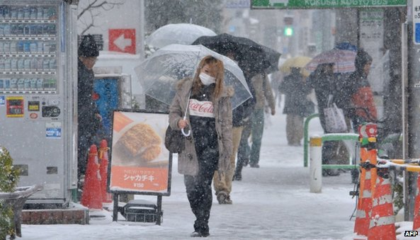 People walk in the snow in Tokyo (8 February 2014)