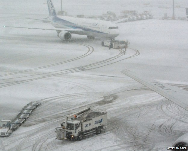 "A jetliner of Japan""s All Nippon Airways (ANA) taxis at Tokyo's Haneda airport covered by the snow on February 8, 2014."
