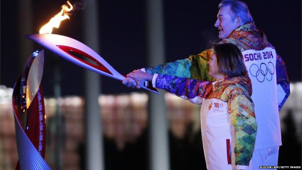 Irina Rodnina (L) and Vladislav Tretyak light the Olympic cauldron.