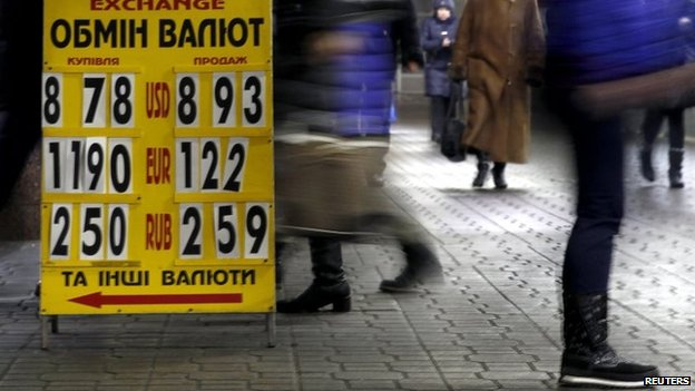 A display showing currency exchange rates is pictured in a subway in central Kiev on Friday