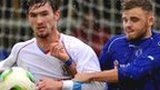 Ballymena's Michael McLellan holds off Dungannon player Fra Brennan