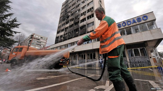 Worker cleans road in front of burned government building in Tuzla on 8 February 2014