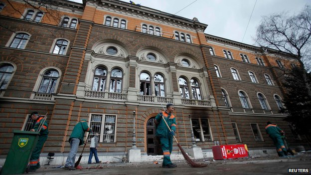 Workers clean up outside a government building in Sarajevo on 8 February 2014