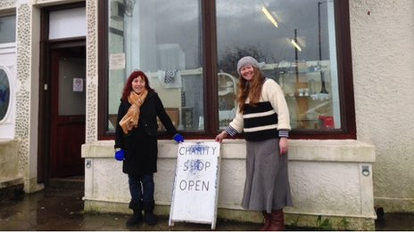 Two women stand outside a charity shop