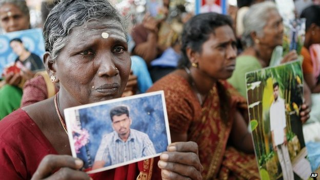 Sri Lankan ethnic Tamil women cry holding portraits of their missing relatives during a protest in Jaffna, Sri Lanka