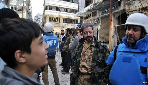 Members of a UN and Syrian Red Crescent team talk with Syrians after entering a besieged district of Homs on Saturday (8 February 2014)
