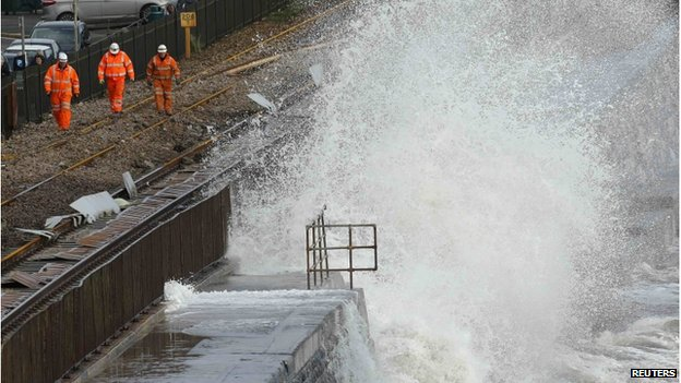 A wave crashes onto a damaged section of railway track, as repair workers walk nearby