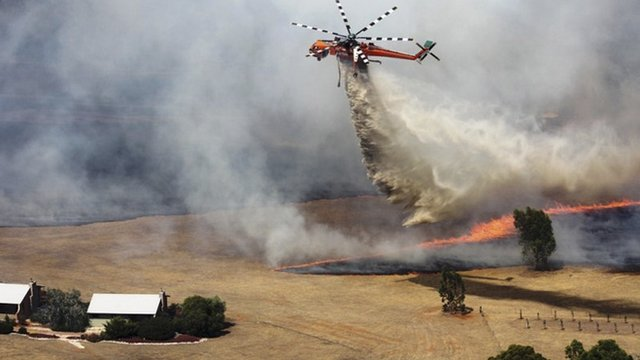 A water bomber in Victoria's Grampians region works to extinguish a large fire