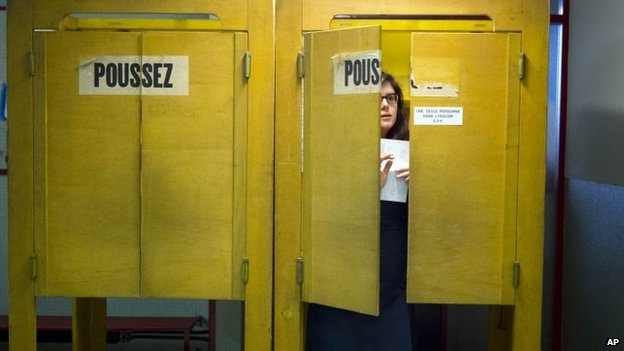 A Swiss voter leaves a polling box at a makeshift polling station