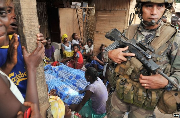 A French soldier stands near a family group mourning their dead in Bangui, CAR, 9 February
