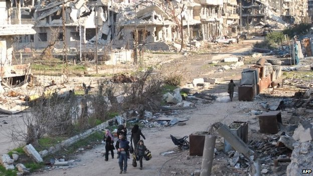 Civilians leave the the besieged district of the central Syrian city of Homs ahead of being evacuated by United Nations staff on 9 February 2014