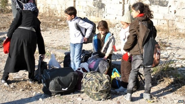 Civilians wait to be evacuated by United Nations staff from the besieged district of the central Syrian city of Homs 9 February 2014
