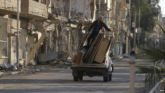 A pick-up truck loaded with belongings drives past damaged buildings in Syria's eastern town of Deir Ezzor (9 February 2014)