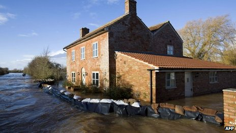 A house surrounded by sandbags - with flood water on both sides of the barrier