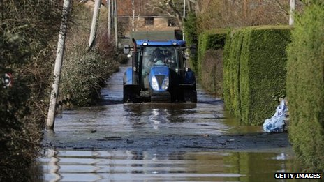 A tractor drives down a flooded road