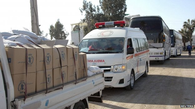 A truck carrying humanitarian aid makes its way to besieged civilians in the old part of Homs