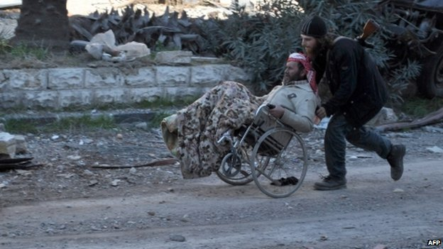 A civilian in a wheelchair is aided by an armed man ahead of being evacuated by the UN from a besieged district of Homs