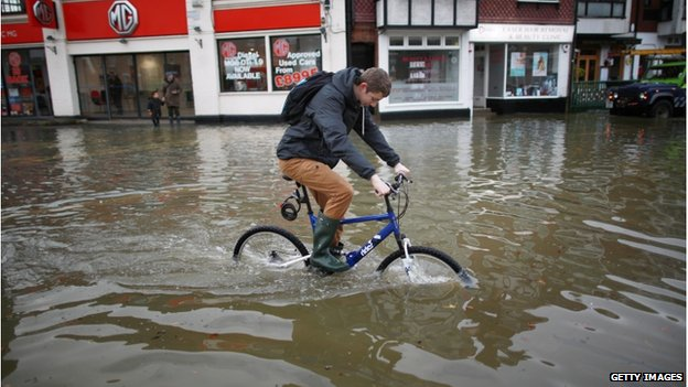 A man struggles to cycle in the flood at Datchet