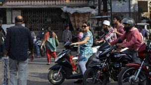 A woman riding a scooter waits for a traffic signal along a street in Mumbai February 5, 2014.