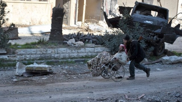 A civilian in a wheel chair is aided by an armed man ahead of being evacuated by United Nations (UN) staff, from the besieged district of the central Syrian city of Homs