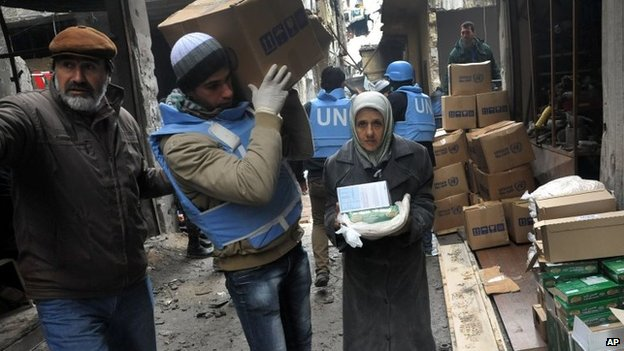 UN relief worker delivers aid inside the Yarmouk refugee camp (4 February 2014)