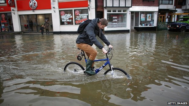 A cyclist rides through floodwater in Datchet