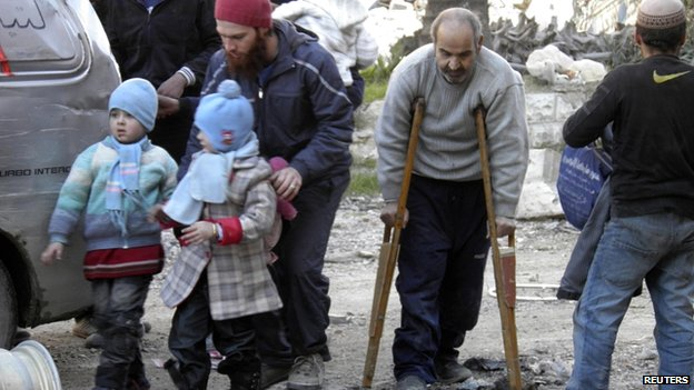 Civilians, including a man with crutches, walk towards a meeting point to be evacuated from Homs on 9 February 2014