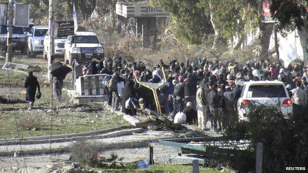 Civilians gather before being evacuated with the help of Syrian Red Crescent and UN personnel from Homs on 9 February 2014