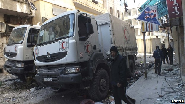 A man walks past damaged Syrian Red Crescent trucks in Homs on 9 February 2014