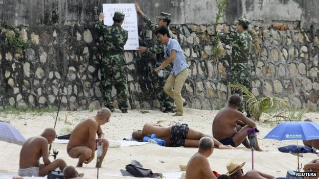 Sunbathers look as government officials put up a notice on banning nudity in public areas, at a beach in Sanya, Hainan province.