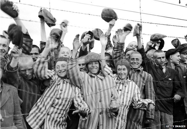 Young prisoners interned at Dachau concentration camp cheering their liberators