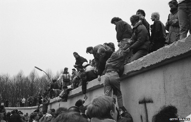East Berliners climb onto the Berlin Wall to celebrate the effective end of the city's partition