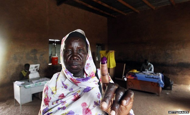 A southern Sudanese woman shows her inked finger after voting at a polling centre in Khartoum