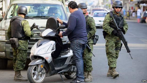 Mexican soldiers check a motorcyclist in Apatzingan, in Michoacan State, on 16 January 16, 2014