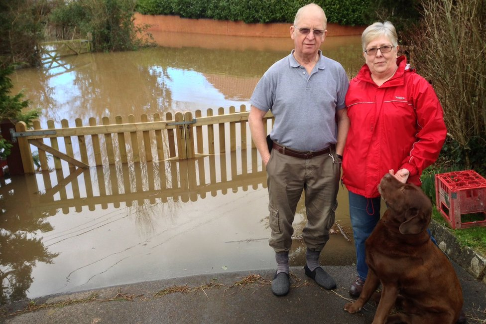 Jennifer and Hywel Jones in front of floodwaters near their house in East Lyng, Somerset