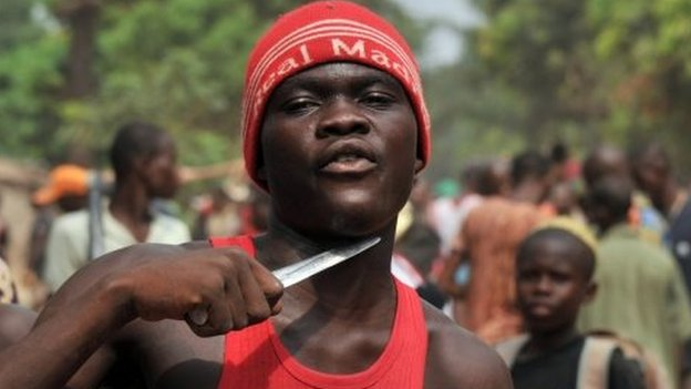 A man holds a knife to his throat claiming that he is looking for Muslims to cut off their heads in the 5th district of Bangui on February 9, 2014.