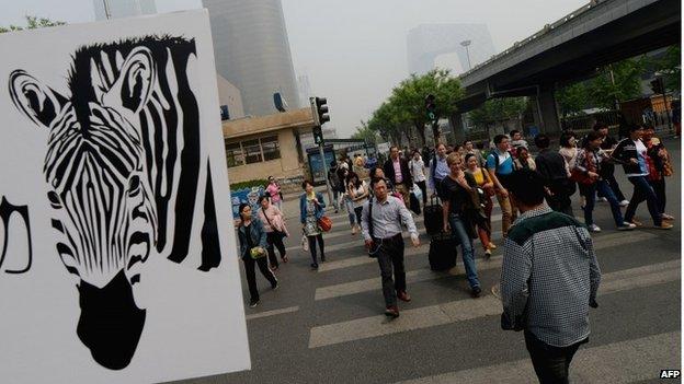 People cross the road in Beijing, May 2013