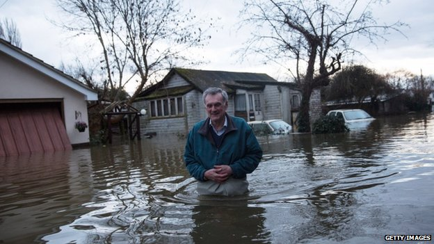 A resident leaves his flood-affected home in Shepperton