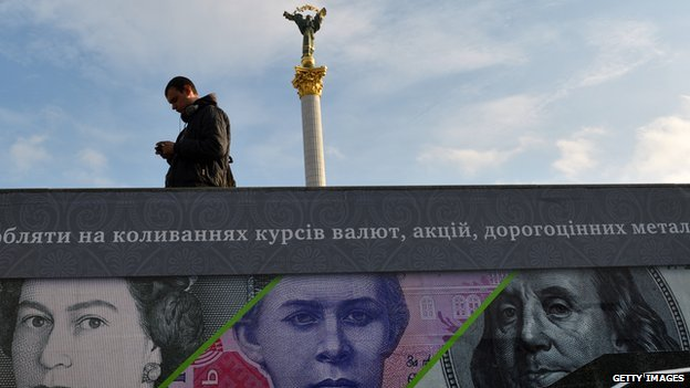 A man stands next to an advertising placard showing British pounds, US dollars and Ukrainian hryvnia banknotes on a warm autumn day in the Ukrainian capital Kiev on 12 November 2012.