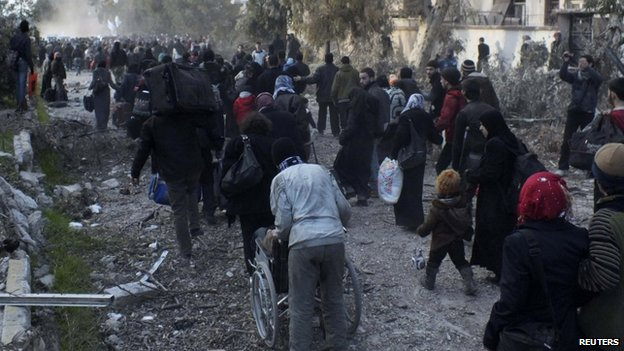 Civilians walk towards a meeting point to be evacuated from a besieged area of Homs on 10 February 2014