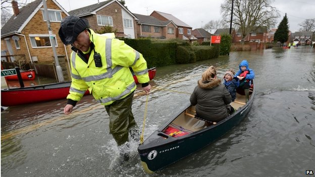 A volunteer helps ferry residents of Purley on Thames, Berkshire