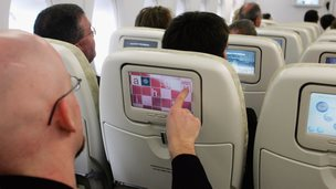 Passengers using in-flight entertainment system on a plane