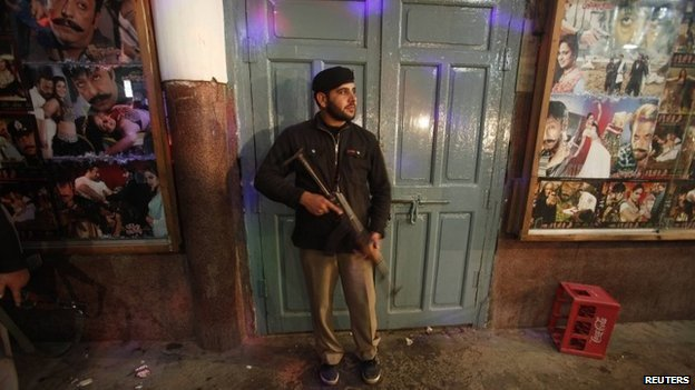 A policeman stands guard at the site of explosions in Peshawar February 2, 2014