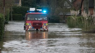 Firefighters drive in a special vehicle through flooding in Wraysbury, Berkshire