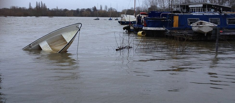 Small boat half-sunk in the flooded Thames