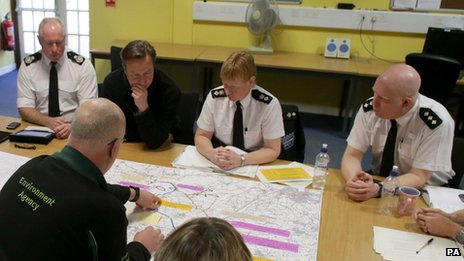 David Cameron is shown a map of flooding as he attends a meeting at Taunton Command Centre